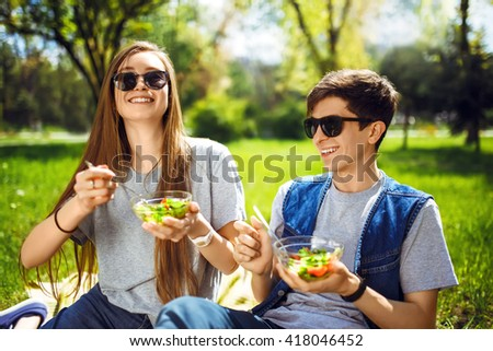 friends enjoying a healthy meal.  Boy and girl eating healthy food. Healthy lifestyle. Concept picnic. Summer time, the setting sun. enjoy the food