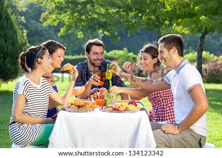 Friends enjoying a relaxing picnic sitting together laughing and chatting at a table in a lush green park - stock photo