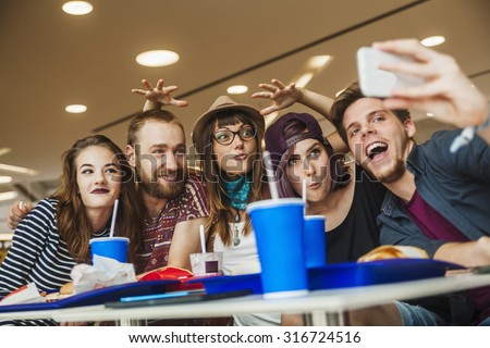Friends Enjoying And Taking Selfie At The Mall - stock photo