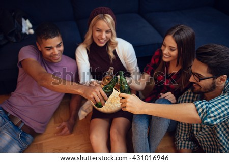Friends enjoying beer and popcorn at home. Selective focus. - stock photo