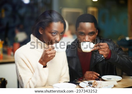 Friends enjoying coffee in beautiful place, cold winter days in beautiful coffee shop, friends at breakfast having coffee and enjoying themselves, two young friends holding cups drink coffee in cafe - stock photo