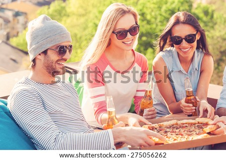 Friends enjoying pizza. Group of young cheerful people eating pizza and drinking beer while sitting at the bean bags on the roof of the building - stock photo