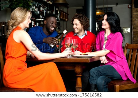 Friends enjoying their dinner with drinks at a restaurant - stock photo