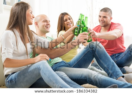 Friends enjoying with beer and cheers together at home party. - stock photo