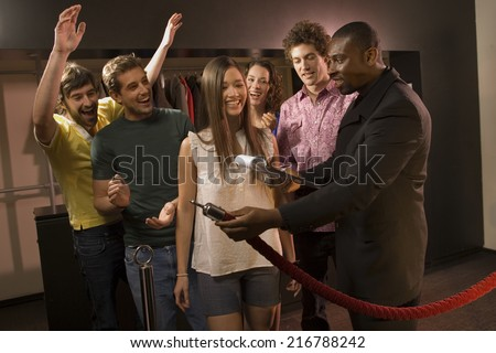 Friends entering a club. - stock photo