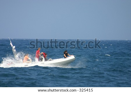 Friends/family on a small speed boat in the sea round Malta, Mediterranean.