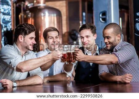 Friends fans drinking beer and watching TV at the bar. Four friends sitting at the table clink glasses with beer in their hands. Friends having fun together - stock photo