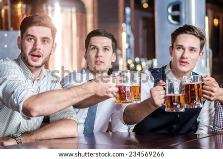 Friends fans getting drunk beer at the bar and watch football on TV. Four friends sitting at the table clink glasses with beer in their hands. Friends having fun together - stock photo