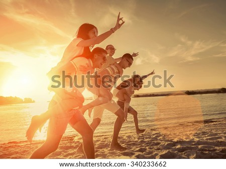 Friends fun on the beach under sunset sunlight.