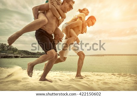 Friends fun on the beach under sunset sunlight. - stock photo