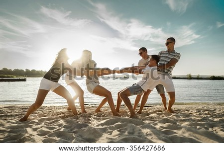 Friends funny tug of war on the beach under sunset sunlight. - stock photo