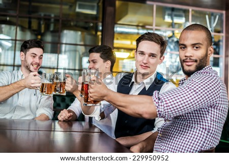 Friends getting drunk beer in the bar. Four friends sitting at the table clink glasses with beer in their hands. Friends having fun together - stock photo