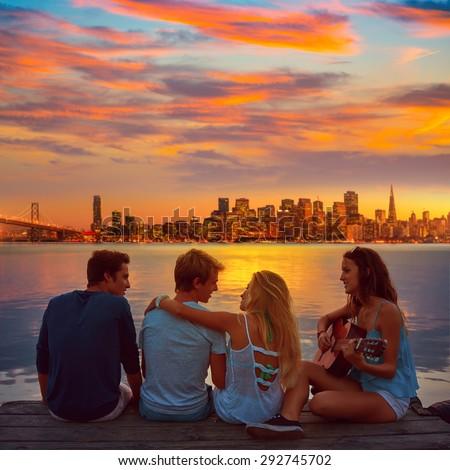 Friends group playing guitar in sunset pier at dusk in San francisco photo mount - stock photo