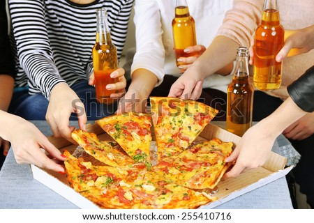 Friends hands with bottles of beer and pizza, close up - stock photo