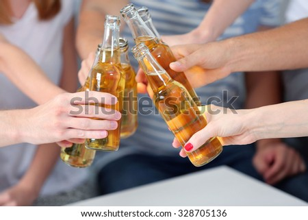 Friends hands with bottles of beer, close up