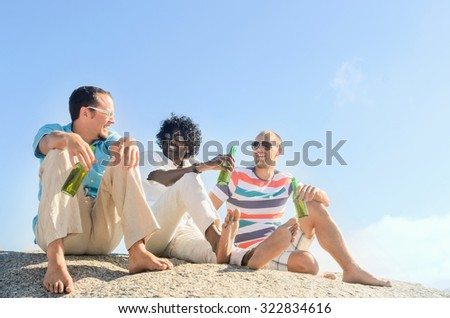 Friends hanging out by the beach drinking beers, enjoying the sunny afternoon, clear blue sky, lots of copy space - stock photo