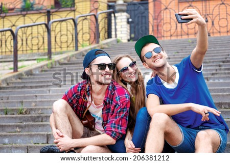 Friends have fun. Young friends have fun together on the street and smile at each other. Funny guys make Selfie - stock photo