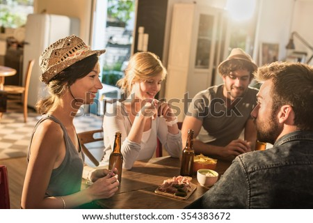 Friends having a drink and playing cards on a sunny evening. They are sitting at a wooden table in a cozy house with beers and tortilla chips. They are smiling, wearing casual clothes and hats. - stock photo