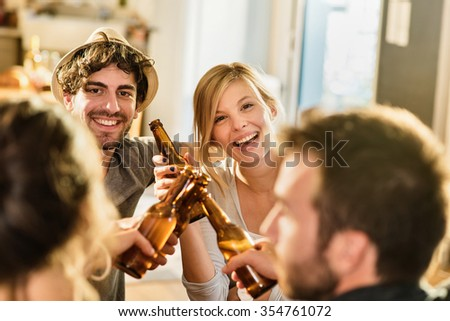 Friends having a drinks on a sunny evening in a cozy house. They are sitting at a wooden table. They are joining their beers. They are wearing casual clothes. Focus on a nice couple in his 30's. - stock photo