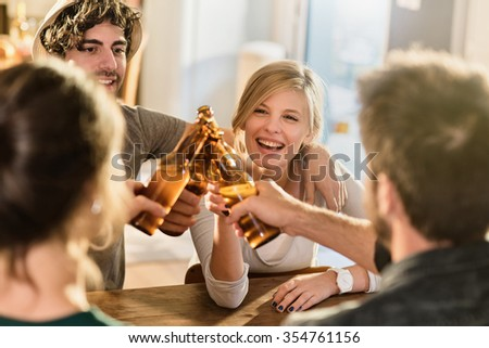 Friends having a drinks on a sunny evening in a cozy house. They are sitting at a wooden table. They are joining their beers. They are wearing casual clothes. Focus on a gorgeous blonde girl. - stock photo