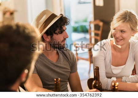 Friends having a drinks on a sunny evening in a cozy house. Two men and a blonde girl are sitting at a table with beers. They are looking at each other, wearing casual clothes. - stock photo