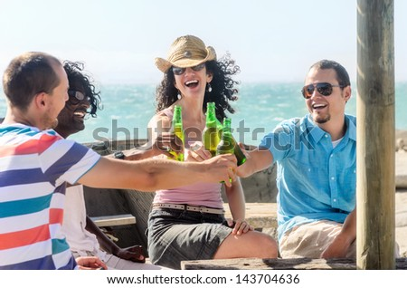 Friends having a round of beers at the beach on a sunny afternoon - stock photo