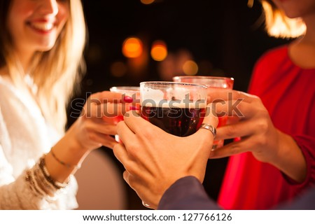 Friends having a round of drinks in a pub - stock photo