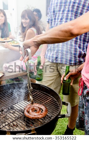 Friends having beers by the bbq at a party, with meat smoking on the hot grill