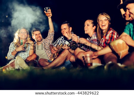 Friends having bonfire party and drinking beer