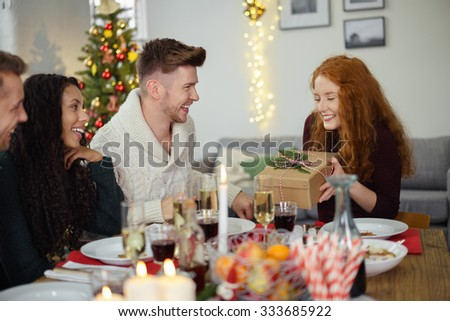 friends having christmas dinner and a man handing a christmas present to his girlfriend