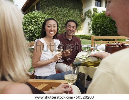 Friends having dinner and drinks in garden - stock photo