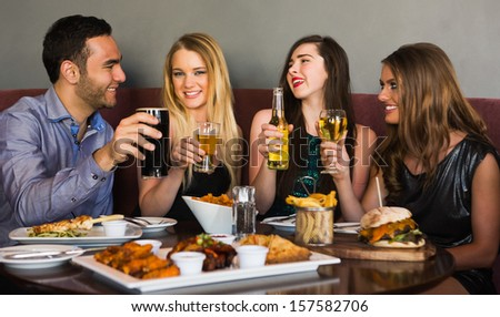 Friends having dinner together and toasting in a restaurant