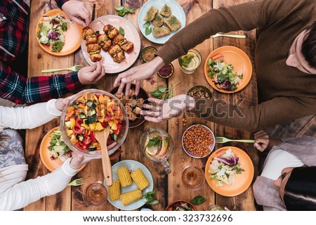 Friends having dinner. Top view of four people having dinner together while sitting at the rustic wooden table - stock photo
