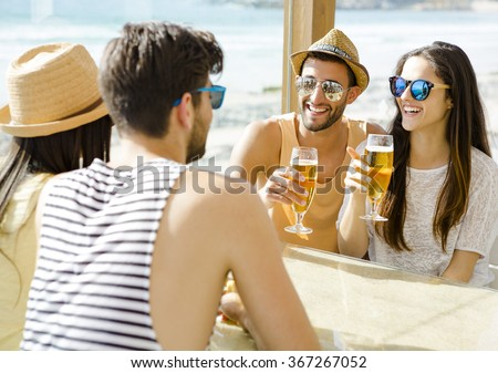 Friends having fun and drinking a cold beer at the beach bar - stock photo