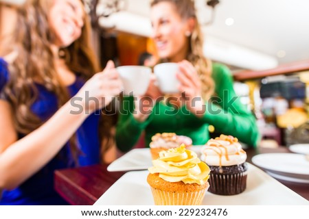 Friends having fun and eating muffins at bakery or pastry shop  - stock photo