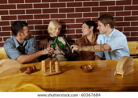 Friends having fun at bar, sitting together at table, having beer, laughing.? - stock photo