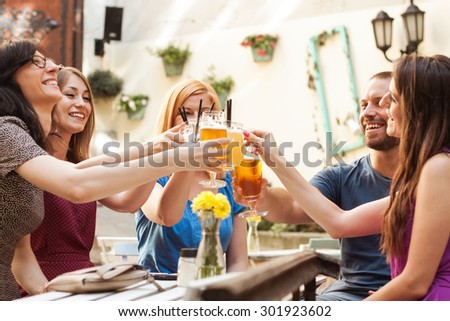 Friends having fun at the bar outdoors, drinking cocktails. - stock photo