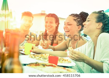 Friends having fun eating pizza at sunset on beach bar restaurant - Cheerful teenagers laughing at dinner party on summer vacation - Concept of joyful meal together Desaturated vintage filter look - stock photo