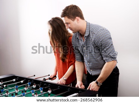 Friends having fun together playing table football. - stock photo