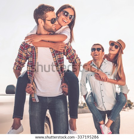 Friends having fun. Two beautiful young couples having fun near their white convertible - stock photo