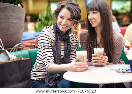 Friends having lunch at a cafe laughing and smiling - stock photo