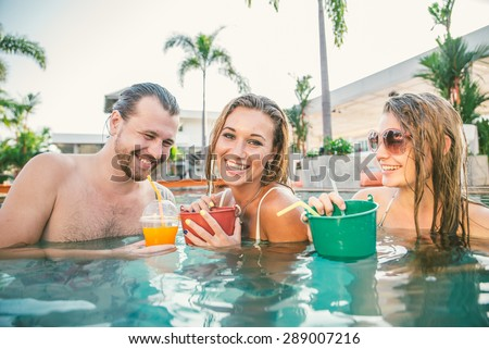 Friends having party and drinking buckets at a swimming pool party - Tourists on vacation in a beautiful tropical resort during summertime - stock photo