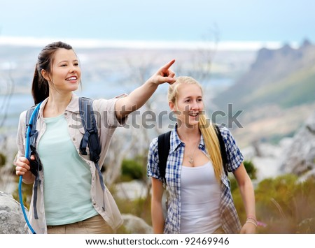 friends hiking together outdoors exploring the wilderness and having fun - stock photo