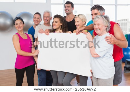 Friends holding blank together in fitness studio - stock photo