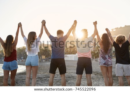 Friends holding hands up together on beach