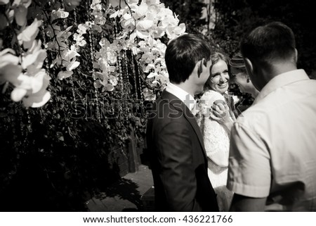 Friends hug newlyweds while they stand behind a wedding altar - stock photo