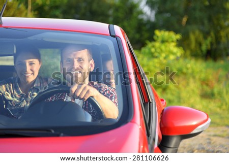 Friends in a red car. Travel freedom concept.