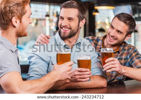 Friends in bar. Three happy young men in casual wear talking and drinking beer while sitting at the bar counter together - stock photo