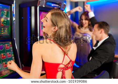 Friends in Casino on a slot machine, all obviously are winning - stock photo