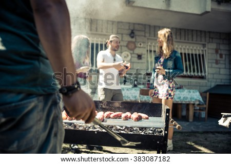 Friends in home garden grilling meat and having fun - Group of people at barbecue party drinking wine - stock photo
